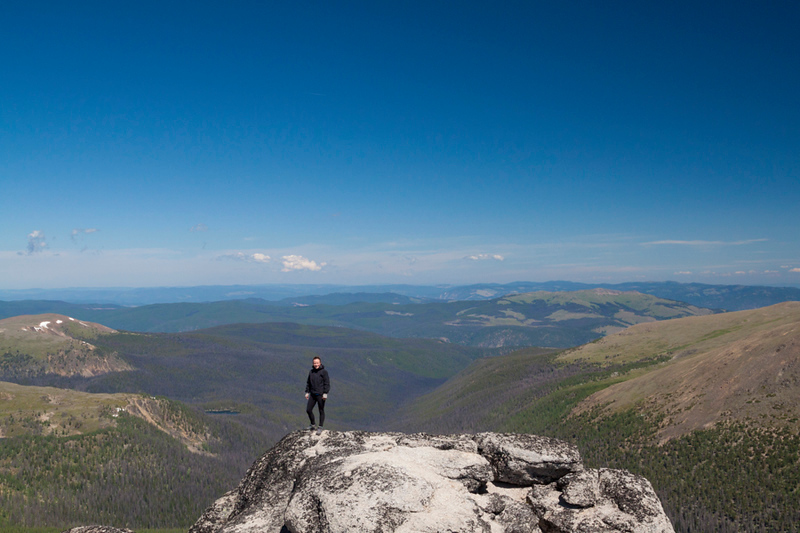A hiker stands on the summit of Grinface Mountain in Cathedral Lakes Provincial Park.