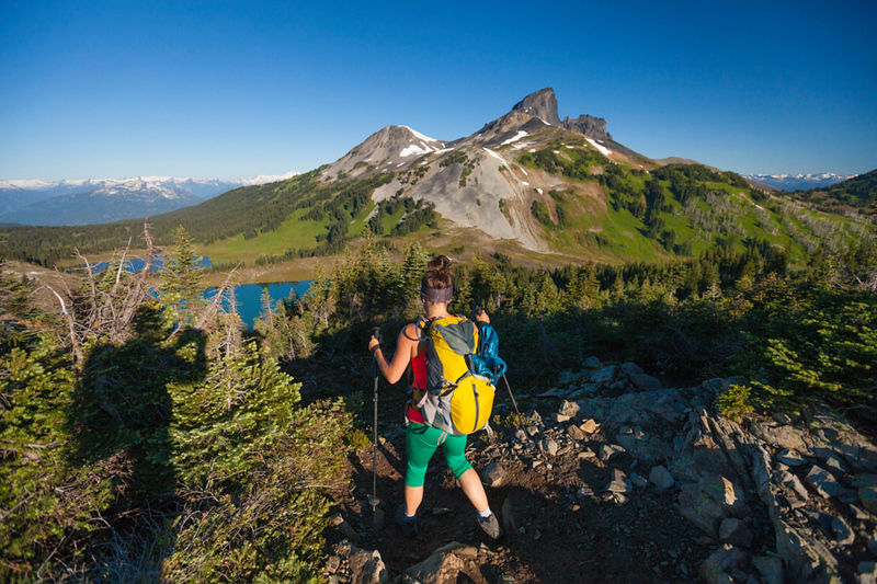 Aphotographer takes a picture of a young woman hiking on the Panorama Ridge Trail in Garibaldi Provincial Park, British Columbia, Canada.