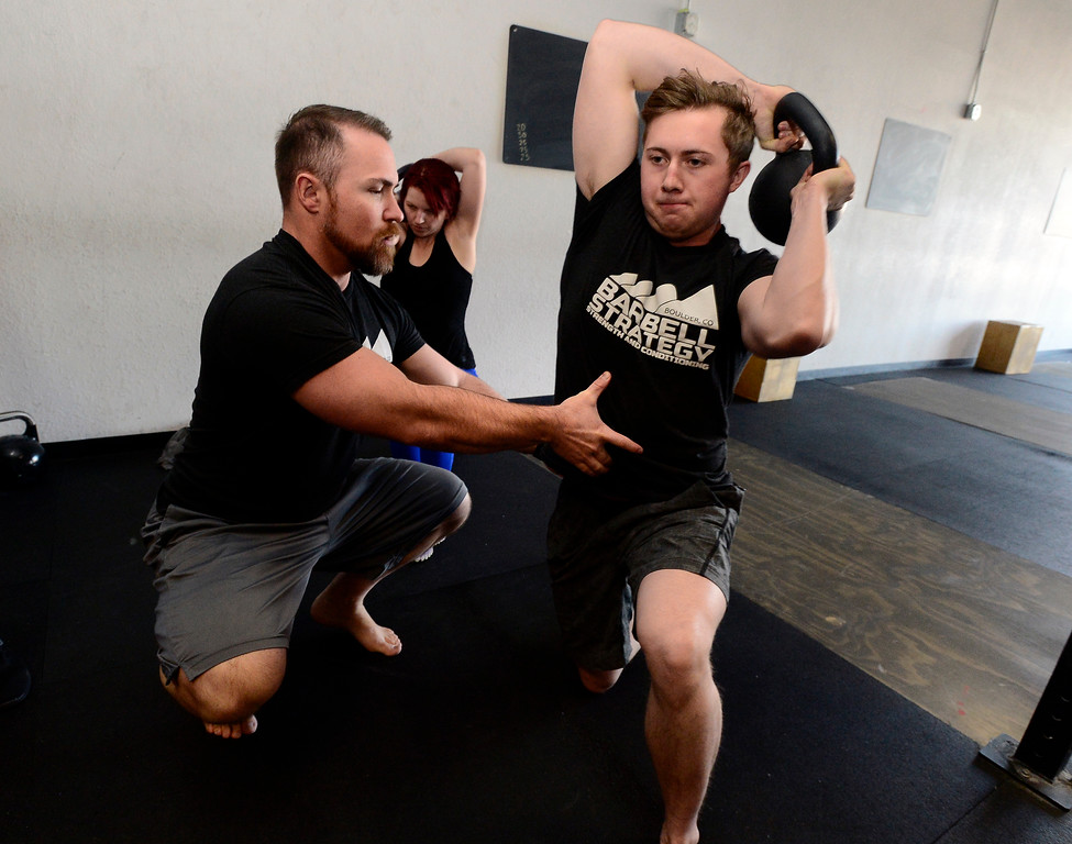 . Instructor Jeremy Layport checks Josh Bowen\'s form as Bowen performs a halo during the Hardstyle Kettlebell class at Barbell Strategy on Monday. For more photos go to dailycamera.com. Paul Aiken Staff Photographer Nov 20 2017