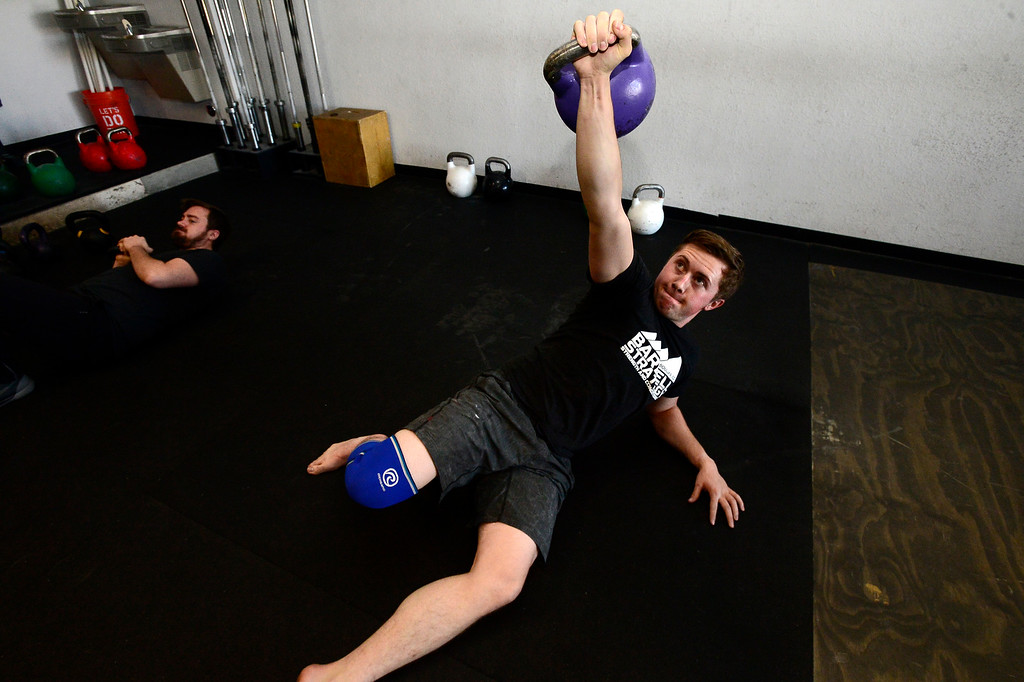 . Josh Bowen performs a Turkish Get Up during the Hardstyle Kettlebell class at Barbell Strategy on Monday. For more photos go to dailycamera.com. Paul Aiken Staff Photographer Nov 20 2017