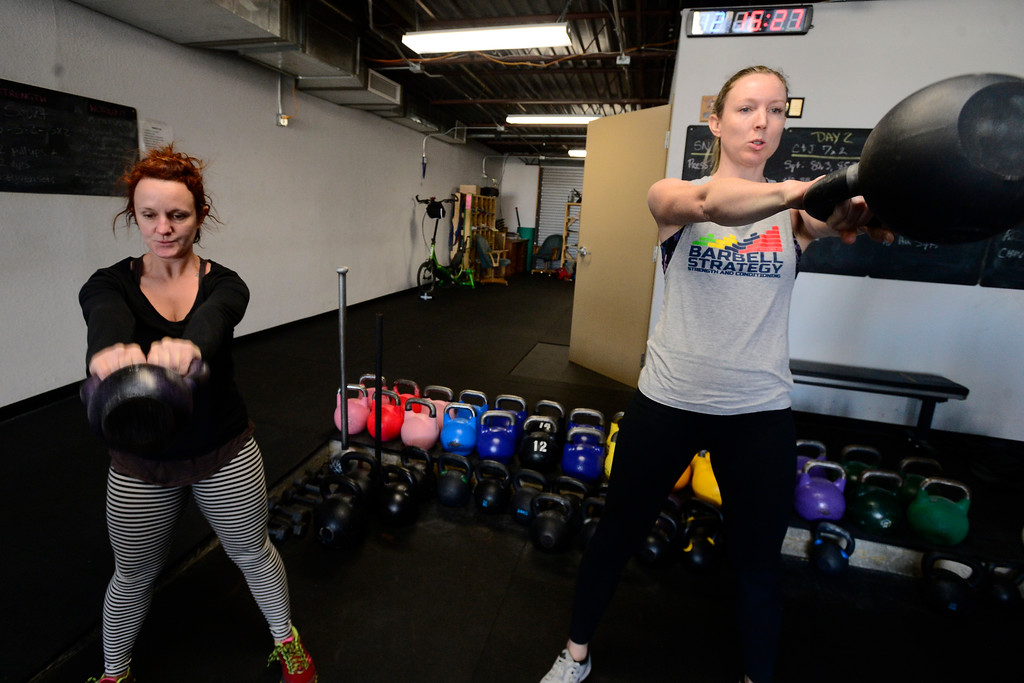 . Sarah Schumacher and Lauren Sullivan perform swings during the Hardstyle Kettlebell class at Barbell Strategy on Monday. For more photos go to dailycamera.com. Paul Aiken Staff Photographer Nov 20 2017