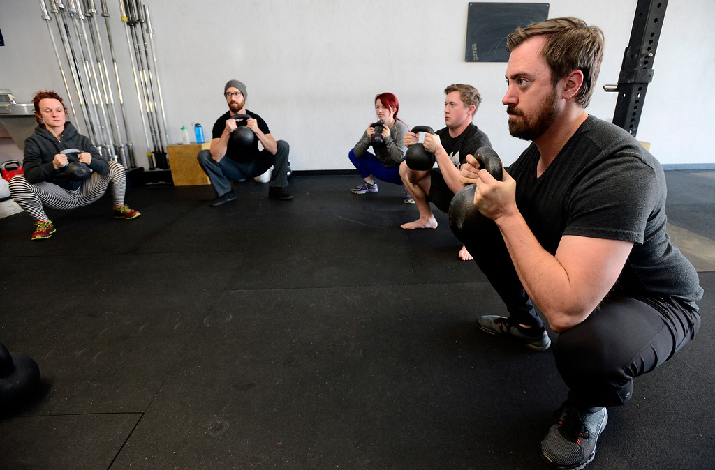 . The class including James Lengyel, at right, perform a warmup kettle squat during the Hardstyle Kettlebell class at Barbell Strategy on Monday. For more photos go to dailycamera.com. Paul Aiken Staff Photographer Nov 20 2017