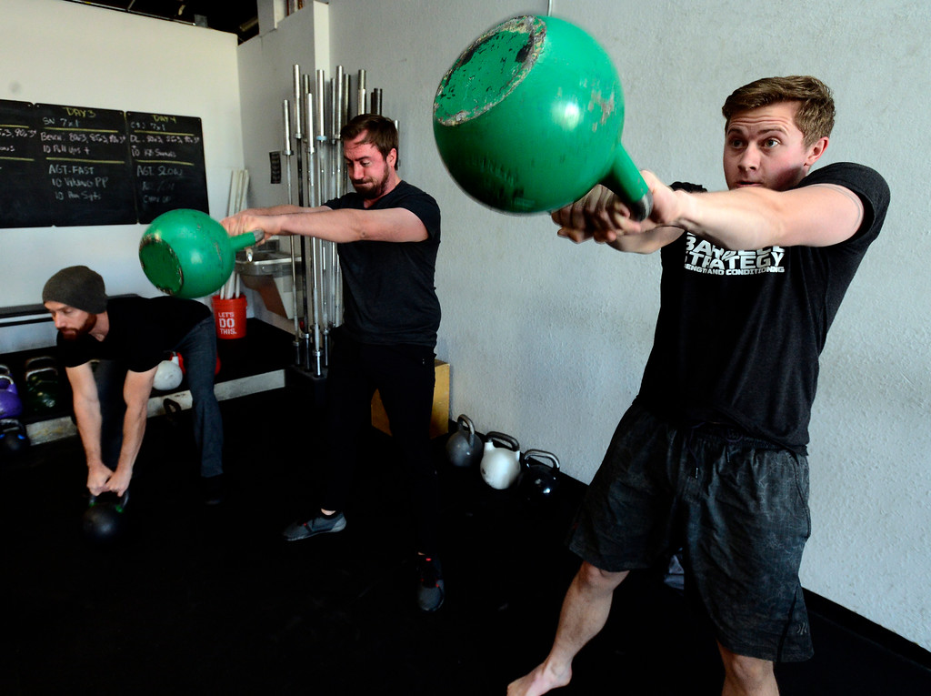 . From left to right Todd Sullivan, James Lengyel, and Josh Bowen perform swings during the Hardstyle Kettlebell class at Barbell Strategy on Monday. For more photos go to dailycamera.com. Paul Aiken Staff Photographer Nov 20 2017