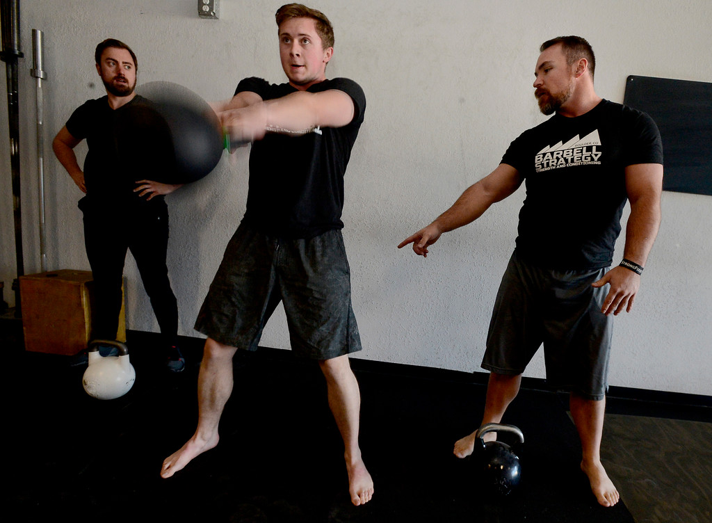 . Instructor Jeremy Layport checks Josh Bowen\'s form during the Hardstyle Kettlebell class at Barbell Strategy on Monday. For more photos go to dailycamera.com. Paul Aiken Staff Photographer Nov 20 2017