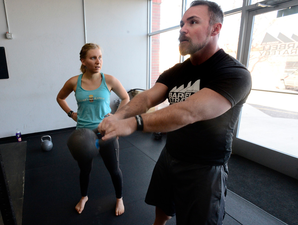 . Instructor Jeremy Layport works with Hannah Moench on her form during the Hardstyle Kettlebell class at Barbell Strategy on Monday. For more photos go to dailycamera.com. Paul Aiken Staff Photographer Nov 20 2017
