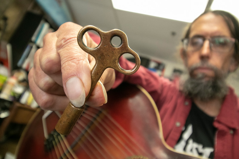 Eddy Troxler the owner of Eddy's Music in Fitchburg shows off the 1918 Gibson U Harp Guitar he just recently got into his shop. Eddy shows off the original key to tune the harp strings on the instrument. SENTINEL & ENTERPRISE/JOHN LOVE
