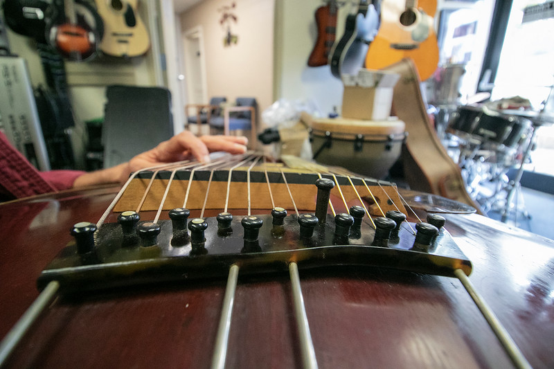 Eddy Troxler the owner of Eddy's Music in Fitchburg shows off the 1918 Gibson U Harp Guitar he just recently got into his shop. This is a close-up of the instuments bridge with it's original ebony bridge pins. SENTINEL & ENTERPRISE/JOHN LOVE