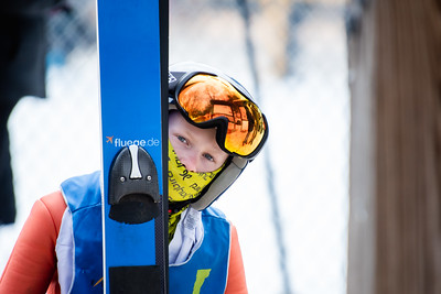 KELLY FLETCHER, REFORMER CORRESPONDENT -- Isak Nichols, peeks around his skis as he awaits transport to the top of the jump at the Fred Harris Memorial Tournament at Harris Hill on Sunday.