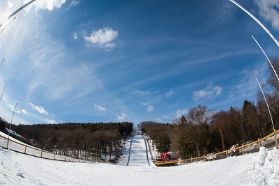 KELLY FLETCHER, REFORMER CORRESPONDENT -- A snow cat idles under a blue sky in the out-run of Harris Hill as one of many preparations in progress for the upcoming competition