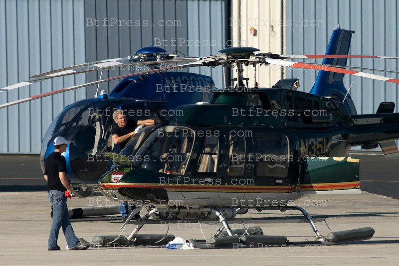 EXCLUSIVE-- Harrison Ford check  and clean the windows of his helicopter before flying in Santa Monica,California.