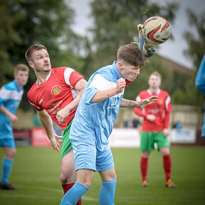 Stephen Bromley reaches up with his foot to contol the ball as the Parkgate defender goes to head it.
