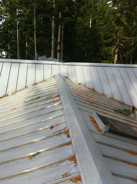 This photo taken from south end of house.   Left is west.  Right is east.  Skylight to right over hallway seems undamaged.   The damaged master bedroom skylight is to the left and you can't see it in this photo. What you can see is that the tree fell from the south to the northeast across the middle ridge vent.