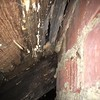 Leak in metal roof near chimney (no proper flashing) has lead to decay of beams