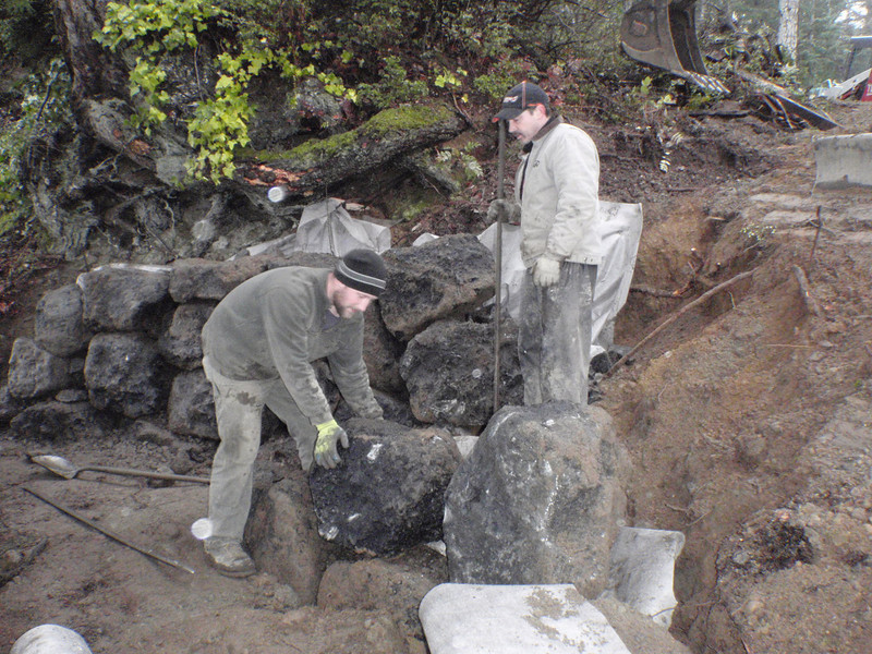 Brian and Charlie.. No Brian did not move that rock by hand.  They used the digging claw on the backhoe to put it close position, then shifted it around with two long bars.   You knew that freshman year physics had to be put to use sometime.