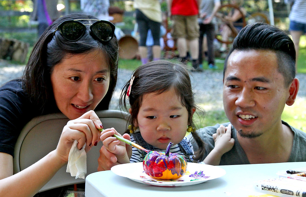 . Painting a small pumpkin at the Harvard Alpaca Ranch open house and tour day is L-R, Jiyu (mother)(note; goes only by one name), daughter Ava Cao 2 1/2, and Long Cao (dad) from Boston. SUN Photo by David H. Brow