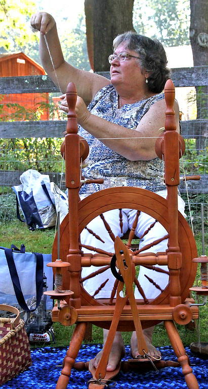 ". Working on spinning alpaca fleece  on the ""Gossip Wheel\"" is Lynn Cooke with the Nashoba Valley Knitter\'s Guild and BASD (Boston Area Spinners & Dyers), at the Harvard Alpaca Ranch. SUN Photo by David H. Brow"