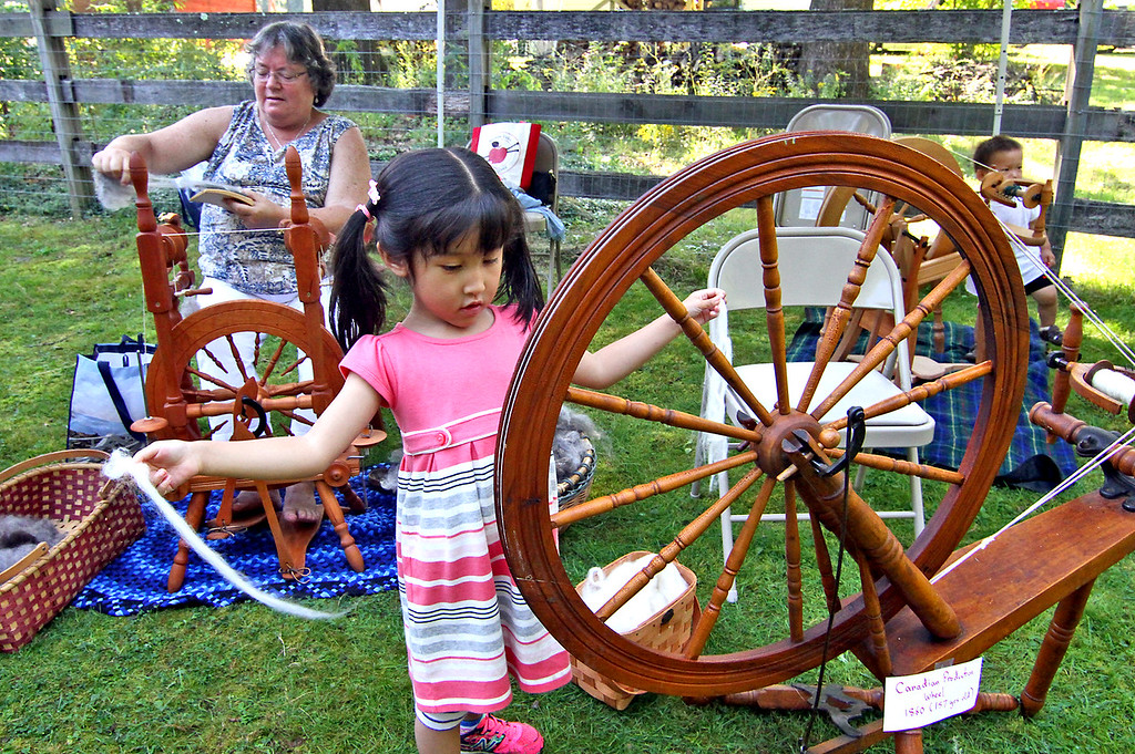 . Shown here trying her hand at Spinning Alpaca fleece is four year old Viola Phu of Andover, in back is member of Nashoba Valley Knitter\'s Guild, Lynn Cooke of Harvard. SUN Photo by David H. Brow