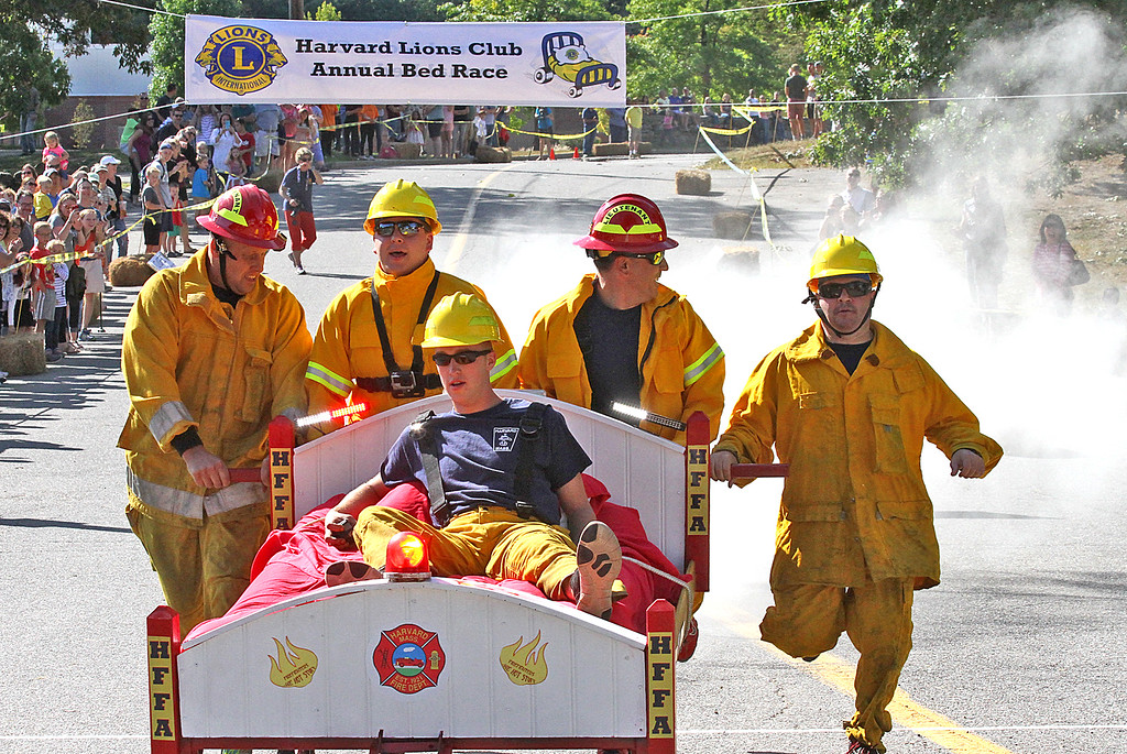 . The FireBalls Team comes over the finish line with lights flashing and a puff of smoke, the Harvard firefighters team took 3nd place and best theme trophy. Nashoba Valley Voice Photo by David H. Brow