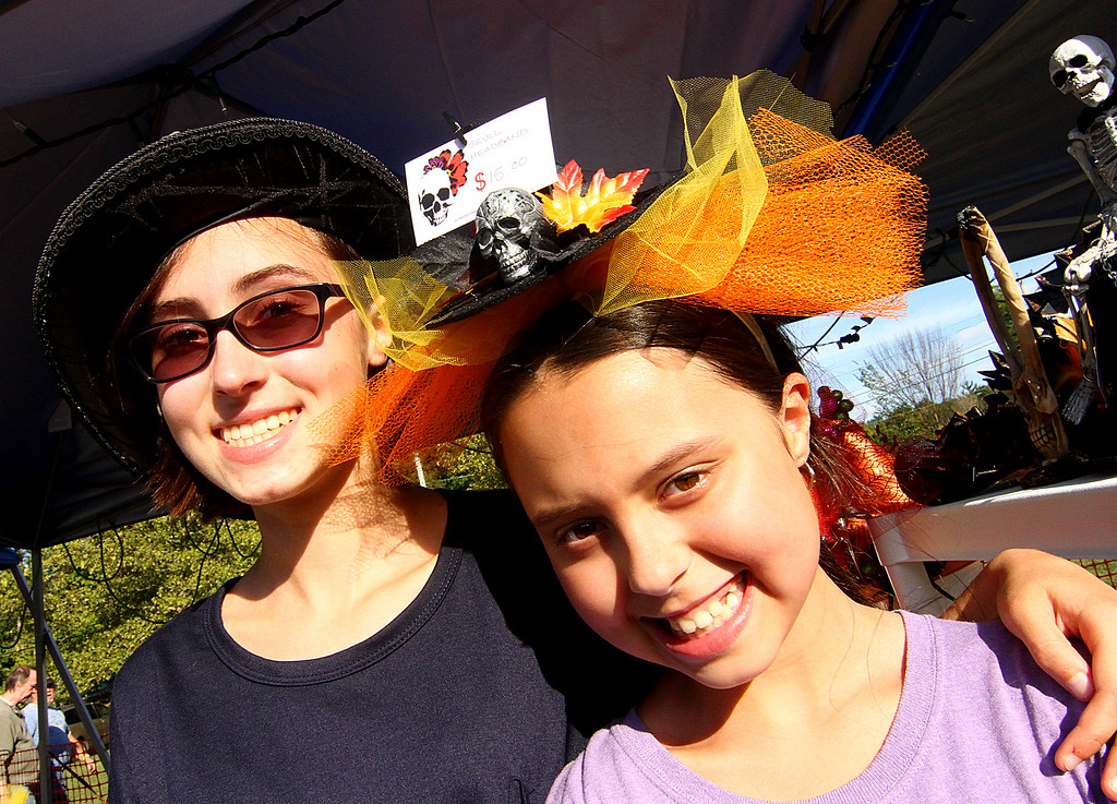 . Trying on seasonal hats from the Scream Punk & Witchy Poo, Inc booth are sisters L-R, Emily Rypinski,14 and Sophia Rypinski,10, from Harvard. Nashoba Valley Voice Photo by David H. Brow