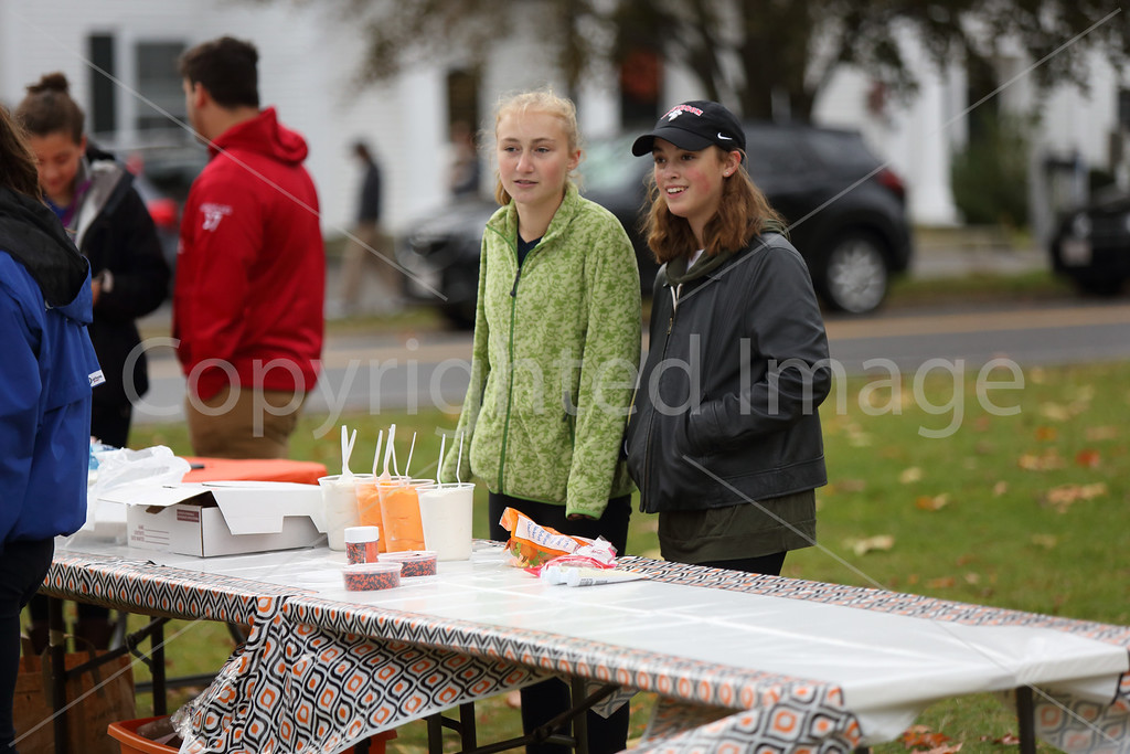 Liza Toll and Grace Acton watch the parade go by as they wait to help with children's crafts.