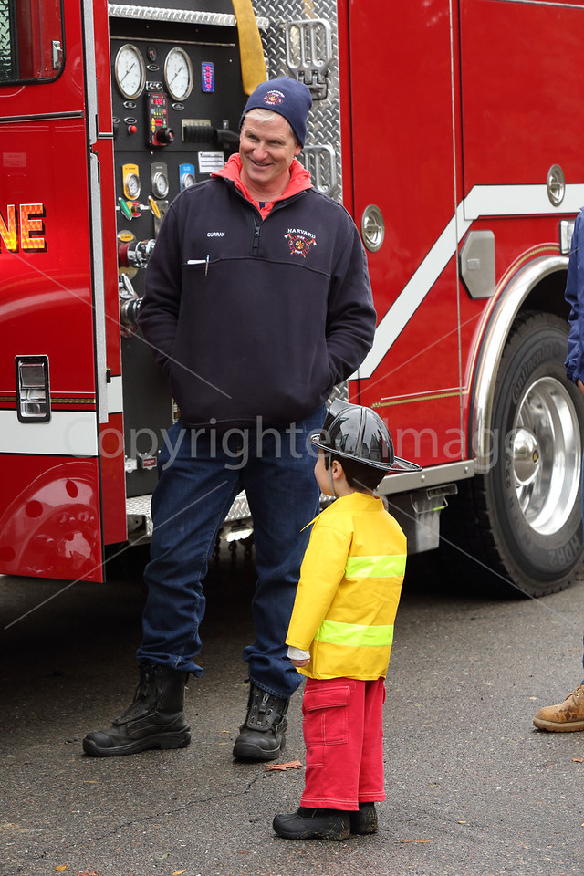 Fire fighter Robert Curran shows off a fire truck to the next generation firefighter, Charlie Hughes.
