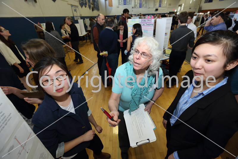 """Sisters Felicia (left) and Julia (right) Deng explain their project """"Gravitational Waves: Theory and Detection,"""" to judge Eileen Myers."""