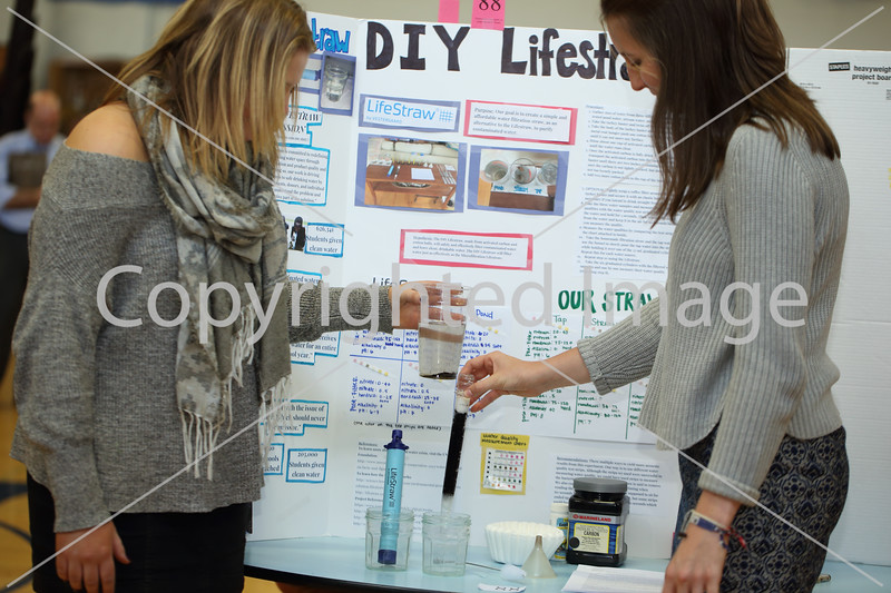 Saddie Flanagan (left) pours water through a homemade filter held by Katie Seavey-Walker to show how pond water can be filtered with a do-it-yourself lifestraw filled with activated carbon to make potable water. Isabelle Lee (not shown) also worked on the project.
