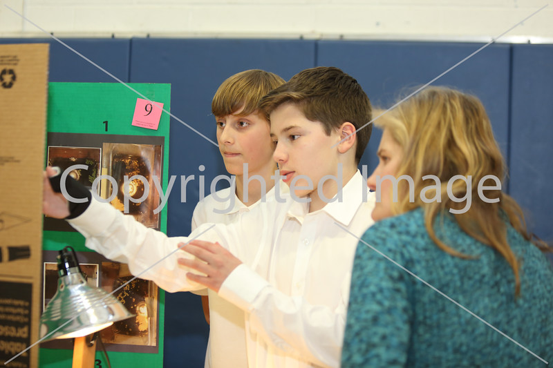 """From left: Gavin Hall and Alex Myles explain their experiment """"Temperatures Effect on Lemna Growth,"""" to judge Leslie Neville."""