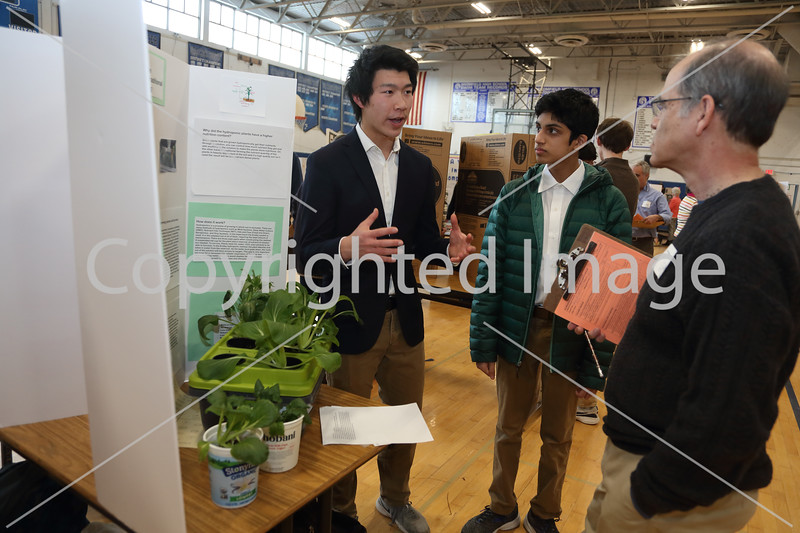 """From left: Science fair partners Jack Yu and Nishkal Pisal explain their project, """"Nuturitional Value in Hydroponics vs. Traditional Soil-based Growing,"""" to judge Jim Adelson."""