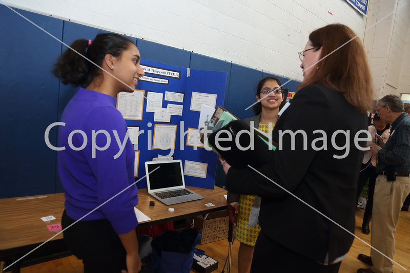 """Shreya Kumar (left) and Raiya Suliman explian their project, """"Keeping Track of Things with PUCK.js,' to Dr. Linda Dwight."""