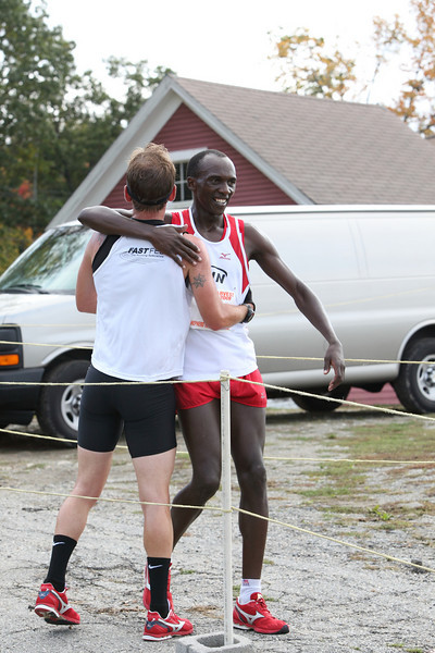 Race winner Michael Brouillette (left) embraces second-place finisher Ben Ndaya at the finish line of the 10-mile Apple Harvest Ramble on October 4 at Fruitlands.