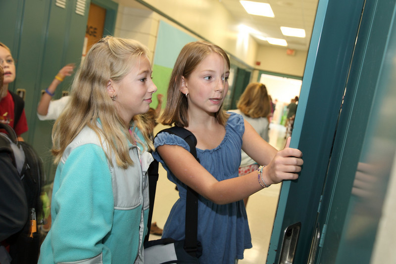 Fourth-graders Carolyn Garvey (left) and Catherine Caruso check out Catherine's new locker.