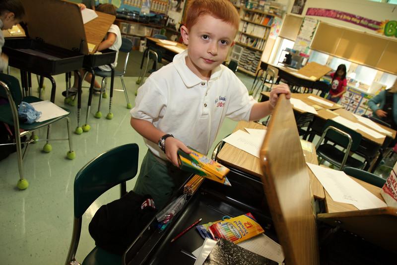 Foruth-grader Samuel Thieme of Devens unpacks his school supplies.