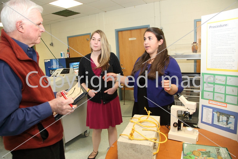 Science fair judge, George Symula, talk with Emily Metzger (center) and Andrea D'Eramo about their project, Diatoms: a Study of Water Health.