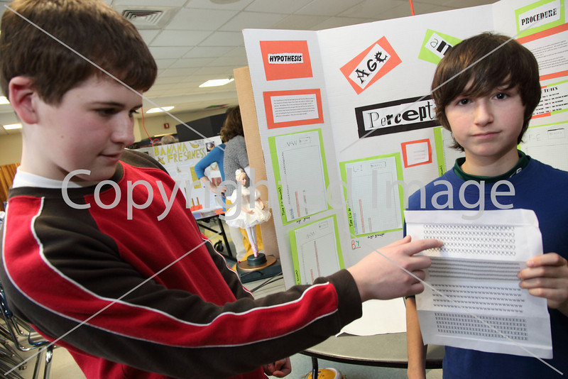 Sixth-graders Ryan Byrne (left) and Thos Brown demonstrate the sheet they used in their experiment on age and perception in which participants had to identify a unique item in a group of the same item.