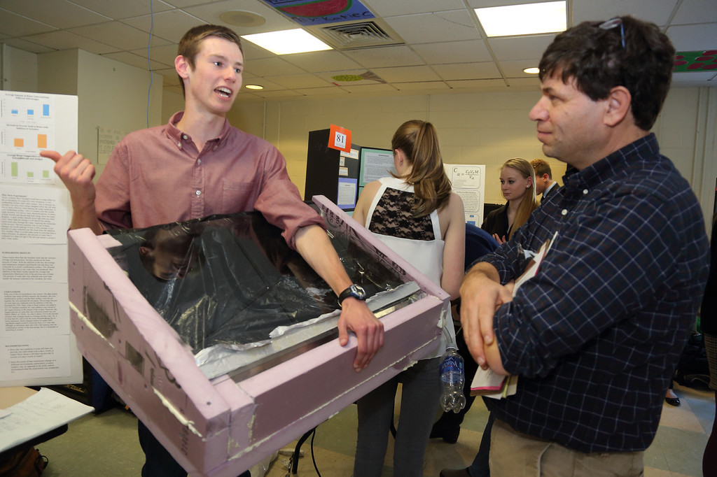 "Junior Nick Steele explains his project ""Solving our Water Problems at Home,"" to judge Pablo Hopman."
