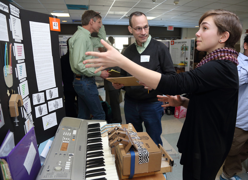 Judge Patrick Sobalvarro listens as Phoebe Clark describes her prosthetic hand project.  The Bromfield Science Fair was held Feb. 27 in the cafeteria.