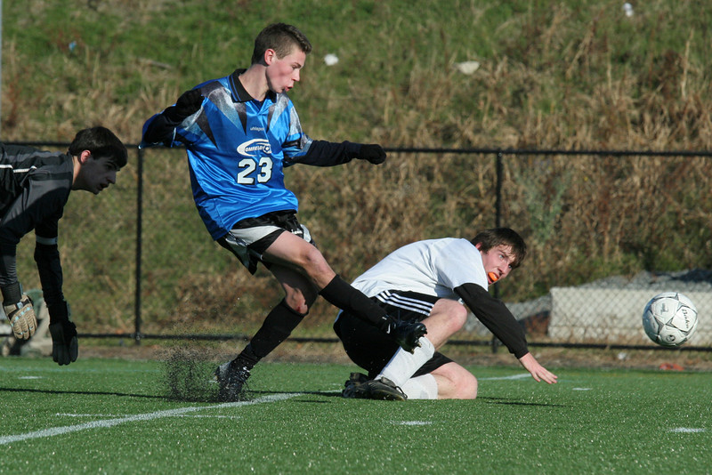 Cody Osgood gets past the Maynard goalkeeper and his teammate to score a goal in the district finals.