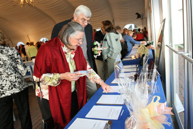 Sue and Jack Guswa check out the silent auction at the COA fashion show held at Fruitlands.