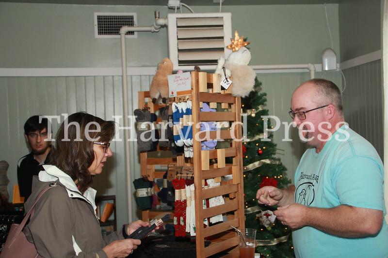 Lynne Hearne asks about some alpaca socks at Matthew Varrell's Alpaca Ranch table.