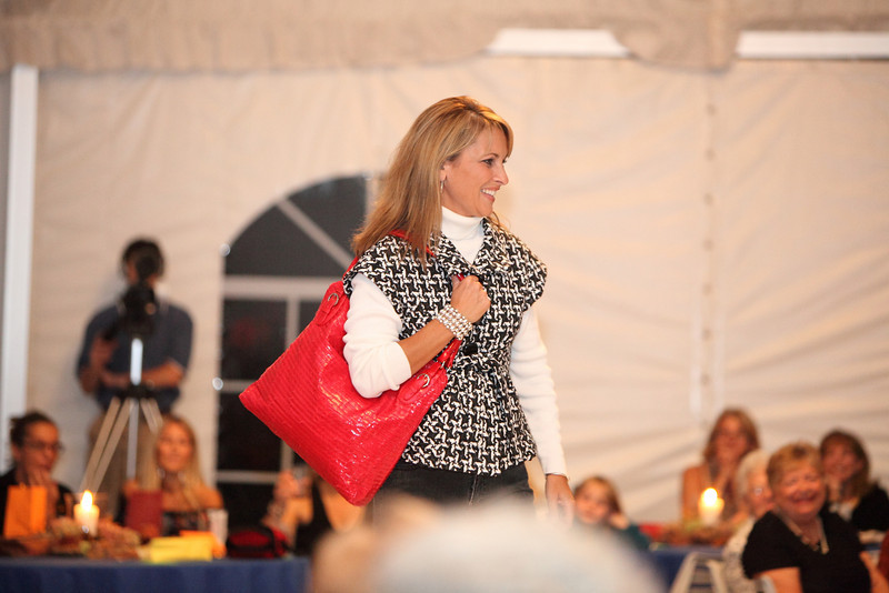 Sherri Armstrong carries a candy apple red fashion patent bag by Bagtique to contrast with her hounds tooth black and white vest.