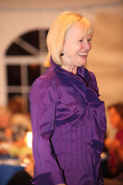 Library Director Mary Wilson looks ready for the holidays in an amethyst-colored ruffled-front blouse by Samuel Dong of New York.