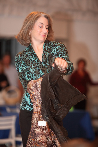 School Committee member Patty Wenger peel off her distressed leather jacket by Montanaco Coat Company to reveal a teal and chocolate leopard print jersey.