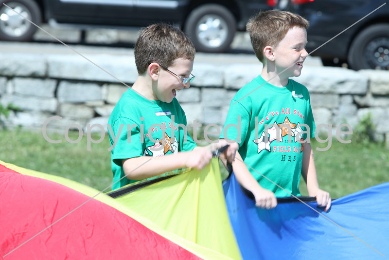 Colin McHugh and Patrick Sullivan hold on to the parachute during a game at field day at the elementary school.
