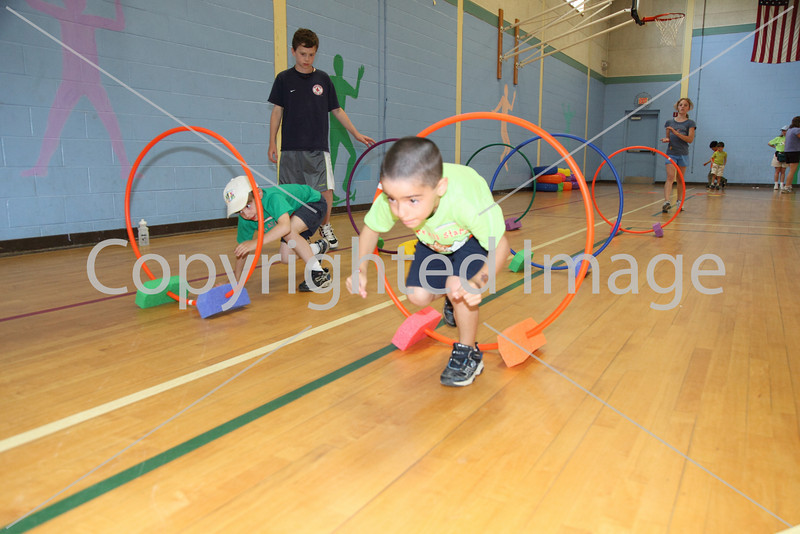 Maxwell McCabe (left) and Daniel Lichtman race through the obstacle course in the elementary school gym on field day.
