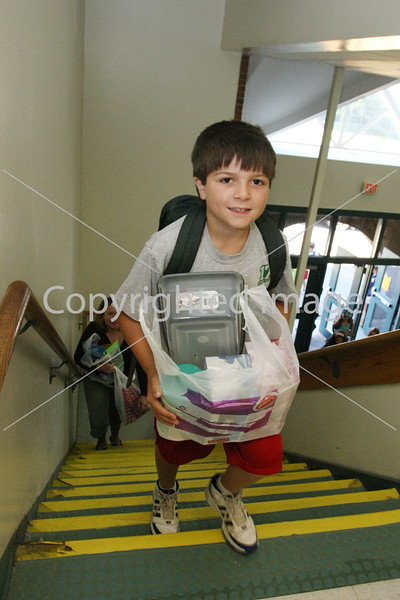 Mikey Brockmann heads up the stairs of the elementary school laden with supplies on the first day of school.
