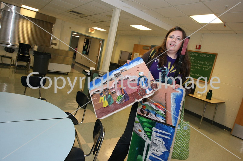 Halsey Berryman shows off ceiling tiles she painted for geography teacher Bryce Mattie.
