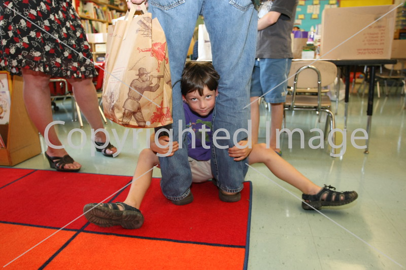 Isaac Noble seeks shelter in his dad's legs at the elementary school open house.