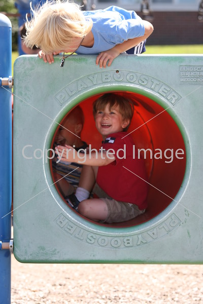 Benjamin Brown and Dylan Winchell play at the elementary school playground as Jack Sennot peaks over the top.