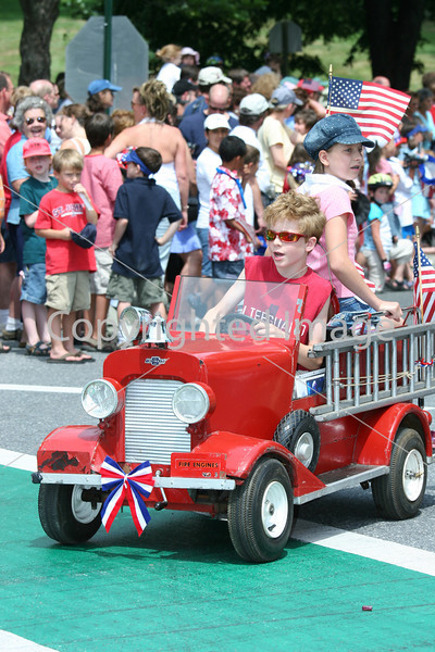 Joseph and Anelise Thibault motor down Mass. Avenue in their mini fire engine.